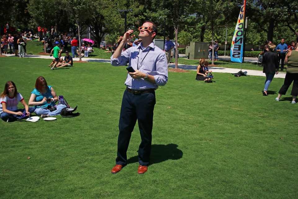 Photo - Mike Moyano views the eclipse through glasses during the great American solar eclipse party on the Great Lawn of the Myriad Botanical Gardens Monday, August 21, 2017. Photo by Doug Hoke, The Oklahoman