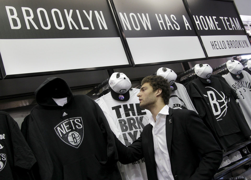 2dbf48618 ... Brooklyn Nets basketball player Brook Lopez looks at team merchandise  before a news conference to unveil ...