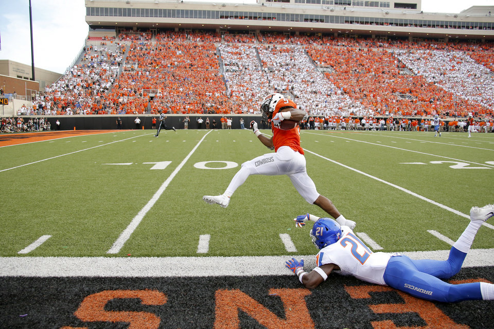 Photo - Oklahoma State's Justice Hill (5) leaps over Boise State's Tyreque Jones (21) after stepping out during a college football game between the Oklahoma State University Cowboys (OSU) and the Boise State Broncos at Boone Pickens Stadium in Stillwater, Okla., Saturday, Sept. 15, 2018. Oklahoma State won 44-21. Photo by Bryan Terry, The Oklahoman