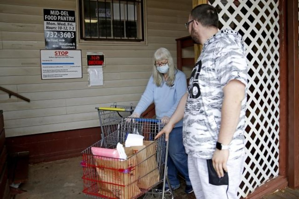 Photo -  Mid-Del Food Pantry volunteer Louise Pickard rolls a basket of food to client Kyle Scott on Friday at the Mid-Del Food Pantry in Midwest City. [Bryan Terry/The Oklahoman]