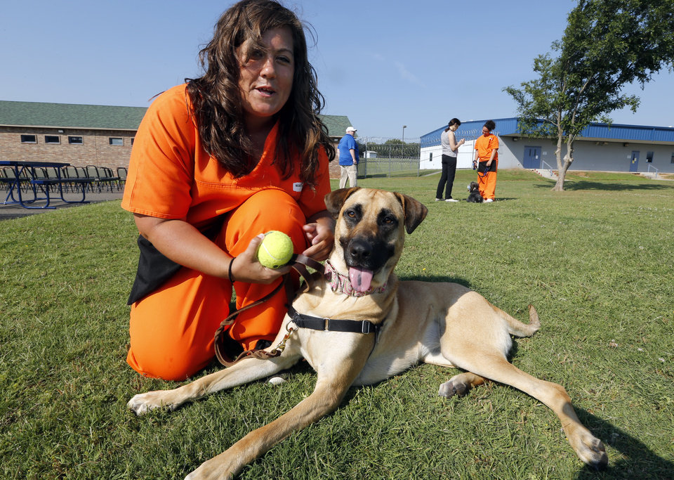 Photo -  Kimberly Wenthold shows her dog in training, Annie, at the new dog training facility. [Photo by Steve Sisney, The Oklahoman]