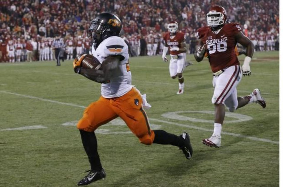 Photo -  OSU's Tyreek Hill returns a punt 92 yards for the game-tying touchdown Saturday in Bedlam. (AP Photo)