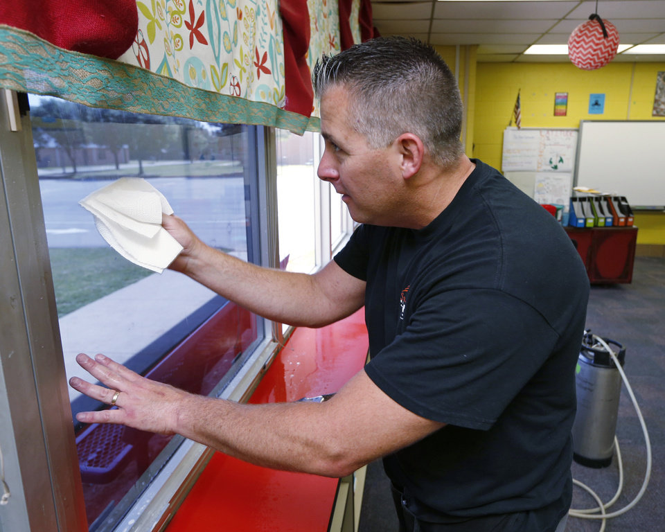 Photo -  Matt Archer works on a one-way reflective window tint at Fairview Elementary School on Monday.