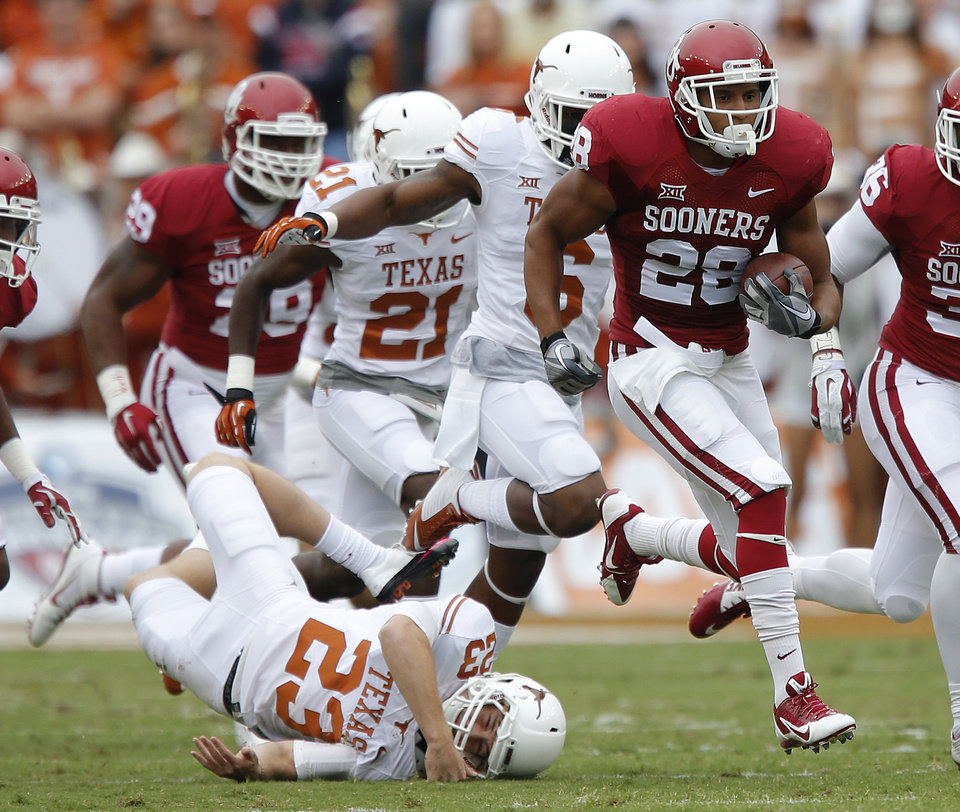 Photo - Oklahoma's Alex Ross (28) runs past Texas' Nick Rose (23) on a kick return for a touchdown during the college football game between the University of Oklahoma Sooners (OU) and the University of Texas Longhorns (UT) during the Red River Showdown at the Cotton bowl in Dallas, Texas on Saturday, Oct. 11, 2014. Photo by Chris Landsberger, The Oklahoman