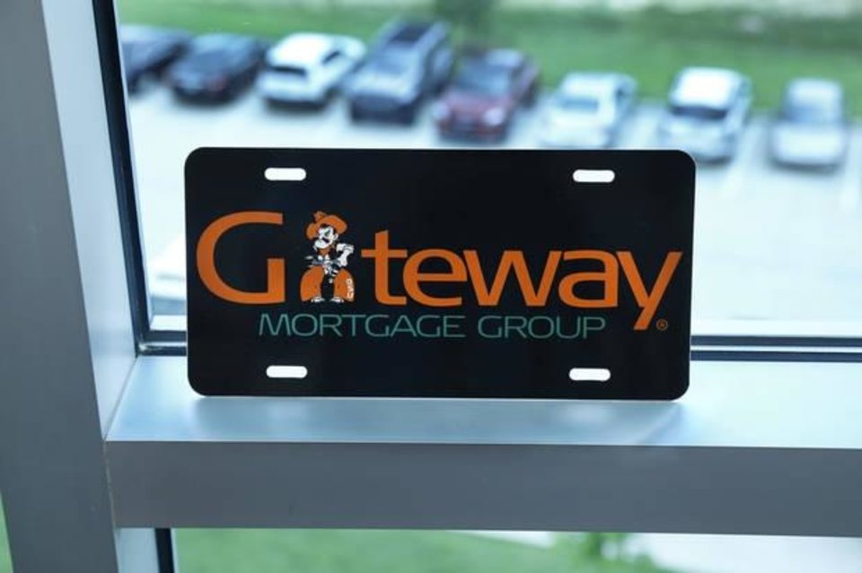 Photo -  This license plate is displayed in an office window at Gateway First headquarters in Jenks. As the founder and former CEO of Gateway Mortgage, Gov. Kevin Stitt's business experience helps shape his governing style as the state's chief executive. During the governor's race, Stitt stepped down as the company's CEO, but what he learned there still influences him today. Photo taken Monday, July 15, 2019.   [Jim Beckel/The Oklahoman]