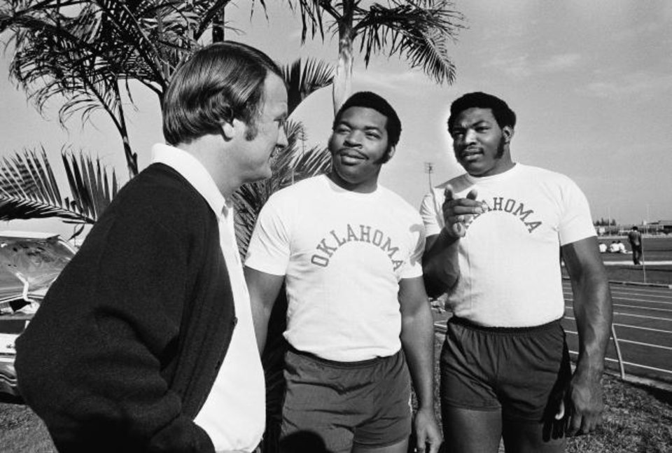Photo -  Coach Barry Switzer was blessed in the 1970s with two top-150 players in brothers Lee Roy Selmon, center, and Dewey Selmon, right. The trio, pictured in Miami on Dec. 27, 1975, led Oklahoma past Michigan in the Orange Bowl for the national title. [AP Photo/Phil Sandlin]