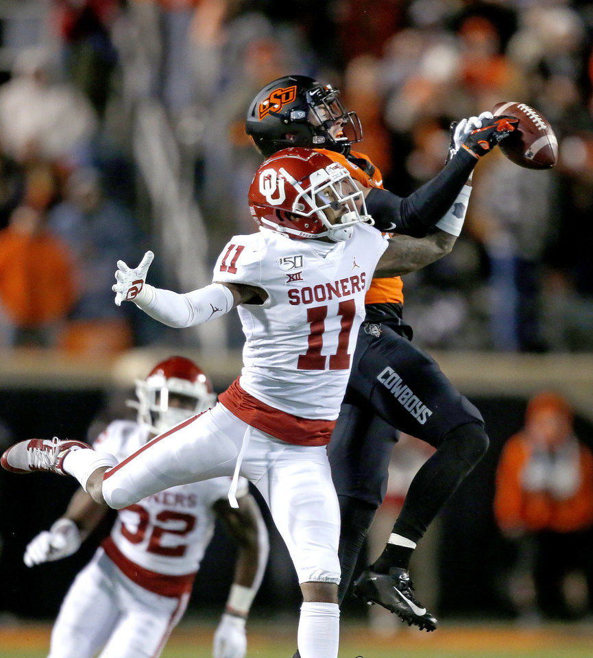 Photo - Oklahoma's Parnell Motley (11) breaks up a pass intended for Oklahoma State's Dillon Stoner (17) in the third quarter during the Bedlam college football game between the Oklahoma State Cowboys (OSU) and Oklahoma Sooners (OU) at Boone Pickens Stadium in Stillwater, Okla., Saturday, Nov. 30, 2019. OU won  34-16. [Sarah Phipps/The Oklahoman]
