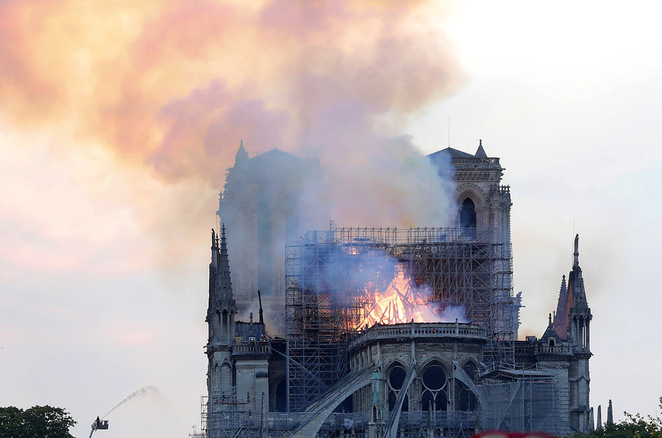 Photo - A firefighter tackles the blaze as flames and smoke rise from Notre Dame cathedral as it burns in Paris, Monday, April 15, 2019. Massive plumes of yellow brown smoke is filling the air above Notre Dame Cathedral and ash is falling on tourists and others around the island that marks the center of Paris. (AP Photo/Thibault Camus)
