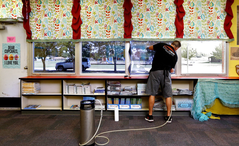 Photo -  Matt Archer works in a classroom at Fairview Elementary to install security film to windows Monday.