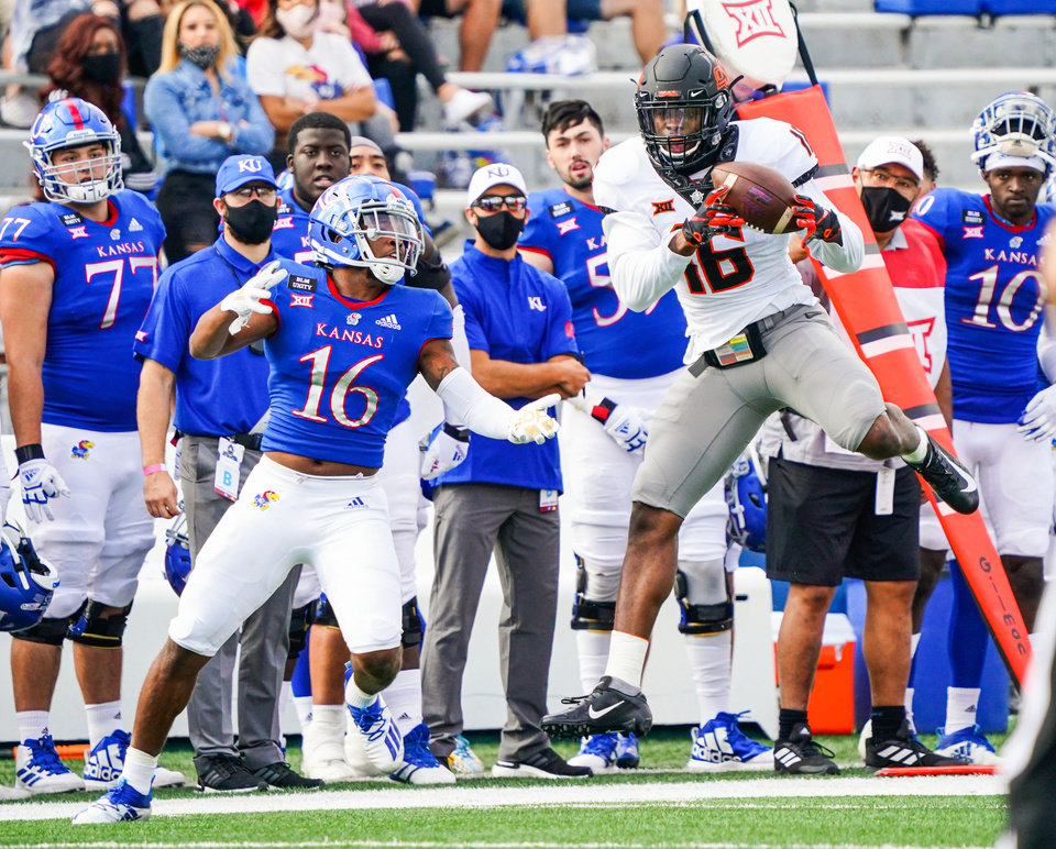 Photo - Oct 3, 2020; Lawrence, Kansas, USA; Oklahoma State Cowboys linebacker Devin Harper (16) intercepts a pass intended for Kansas Jayhawks wide receiver Takulve Williams (16) during the first half at David Booth Kansas Memorial Stadium. Mandatory Credit: Jay Biggerstaff-USA TODAY Sports