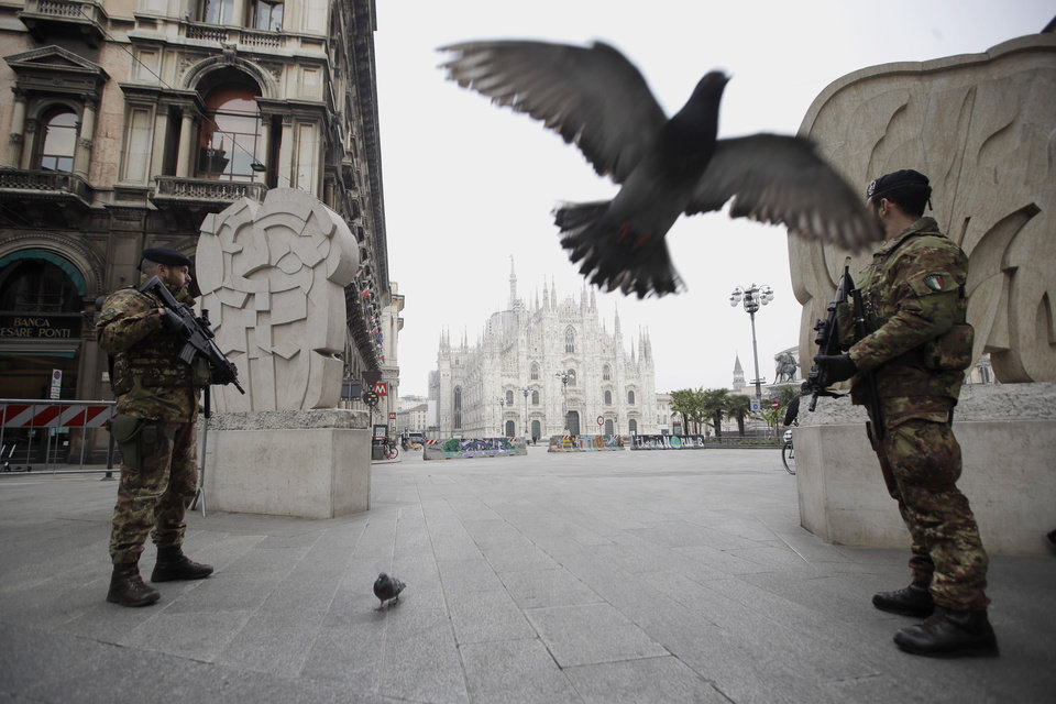Photo -  Italian soldiers patrol as the Duomo gothic cathedral is visible in background, in Milan, Friday, March 20, 2020. Mayors of many towns in Italy are asking for ever more stringent measures on citizens' movements to help contain the surging infections of the coronavirus. For most people, the new coronavirus causes only mild or moderate symptoms. For some it can cause more severe illness. (AP Photo/Luca Bruno)