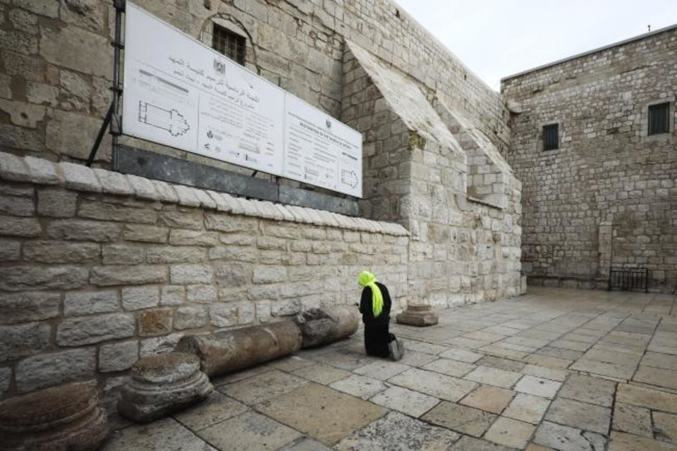 Photo -  A pilgrim prays outside the Church of the Nativity in Bethlehem, West Bank. [AP Photo]