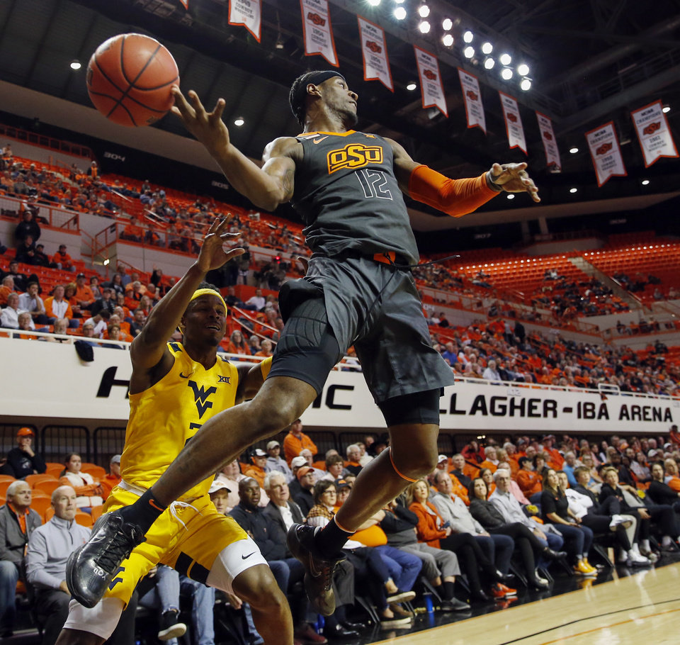 Photo - Oklahoma State's Cameron McGriff (12) loses the ball as he tries to save it from going out of bounds in front of West Virginia's Brandon Knapper (2) in the second half during a men's college basketball game between the Oklahoma State Cowboys and West Virginia Mountaineers at Gallagher-Iba Arena in Stillwater, Okla., Monday, Jan. 6, 2020. West Virginia won 55-41. [Nate Billings/The Oklahoman]