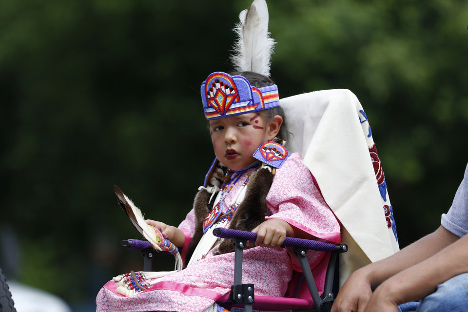 "Photo - LeeAnn ""Pretty Wing"" Pratt watches the crowd as she participates in the parade for the 2019 Red Earth Festival in downtown Oklahoma City, Oklahoma Saturday, June 8, 2019.  [Paxson Haws/The Oklahoman]"