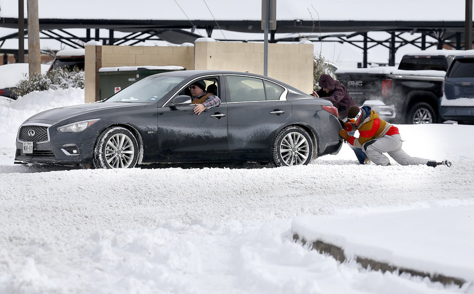 Photo - People push a stuck car near the Broadway Extension in Edmond, Okla., Wednesday, Feb. 17, 2021. [Sarah Phipps/The Oklahoman]
