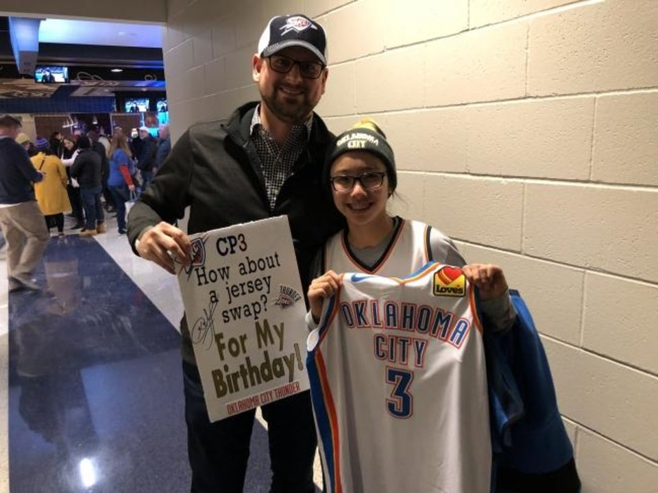 Photo -  Thunder fans Jason and Eva Heardt show off the sign that led to them getting Chris Paul's jersey Wednesday after OKC's win against Cleveland. [JOE MUSSATTO/THE OKLAHOMAN]