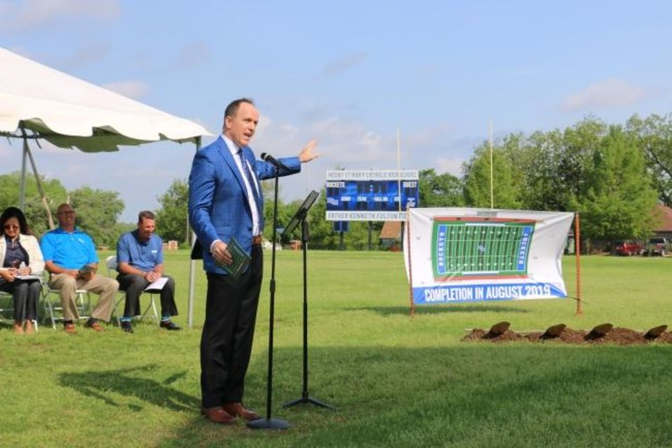 Photo -  Chris Stiles, Mount St. Mary Catholic High School director of advancement, speaks to the crowd about the new football field turf at the groundbreaking ceremony. [PHOTO PROVIDED]