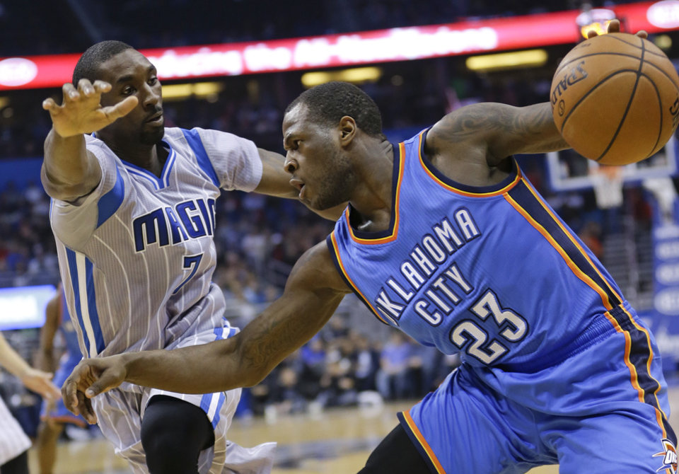 Photo - Oklahoma City Thunder's Dion Waiters (23) makes a move to get around Orlando Magic's Ben Gordon, left, during the first half of an NBA basketball game, Sunday, Jan. 18, 2015, in Orlando, Fla. (AP Photo/John Raoux)
