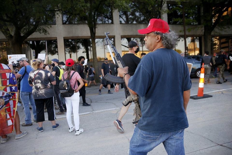 Photo - A Donald Trump supporter watches protesters march past outside the President Donald Trump rally at the BOK Center in Tulsa, Okla., Saturday, June 20, 2020. [Bryan Terry/The Oklahoman]