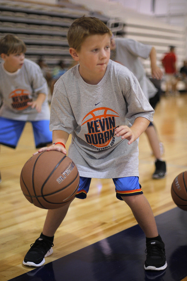 Photo - Braden Roberts, 9 of Oklahoma CIty, participates in a dribbling exercise during the Kevin Durant basketball camp at Heritage Hall Wednesday, June 29, 2011.  Photo by Garett Fisbeck, The Oklahoman