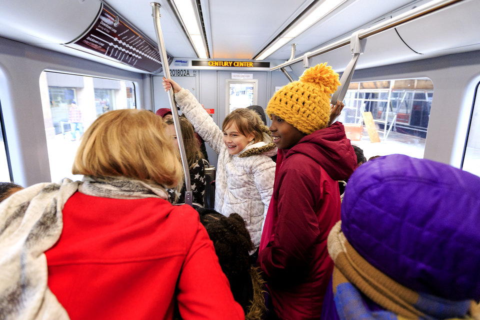 Photo - John Rex Elementary fourth graders Parker Ray, center, and Lolufe Adedeji  ride with his fellow students on the new streetcar during the grand opening celebration day of the Oklahoma City streetcar system in downtown Oklahoma City, Okla. on Friday, Dec. 14, 2018. Photo by Chris Landsberger, The Oklahoman