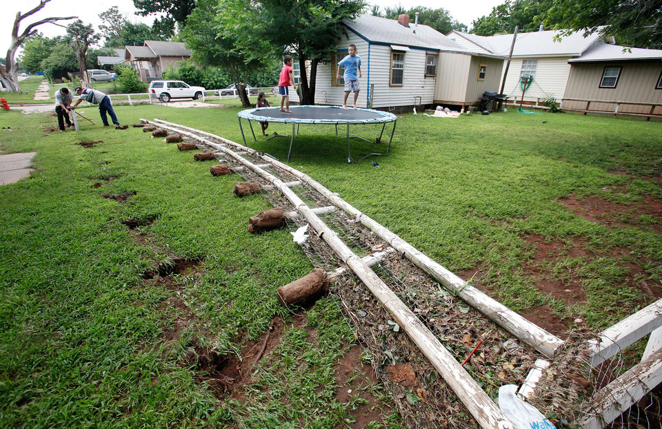Photo - Miguel Sirachio helps friend Roberto Reyas reinstall the fence in the front yard of  Reyas'  home at SW 28 and Broadway. Children play on a trampoline in their yard that was under water last night. Residents cleaned homes and yards in the area near Lightning Creek in south Oklahoma City, Friday, July 9, 2010. Heavy rains last night caused the  creek to overflow its banks, flooding the areas on both sides of the creek.  Staff Photo by Jim Beckel , The Oklahoman