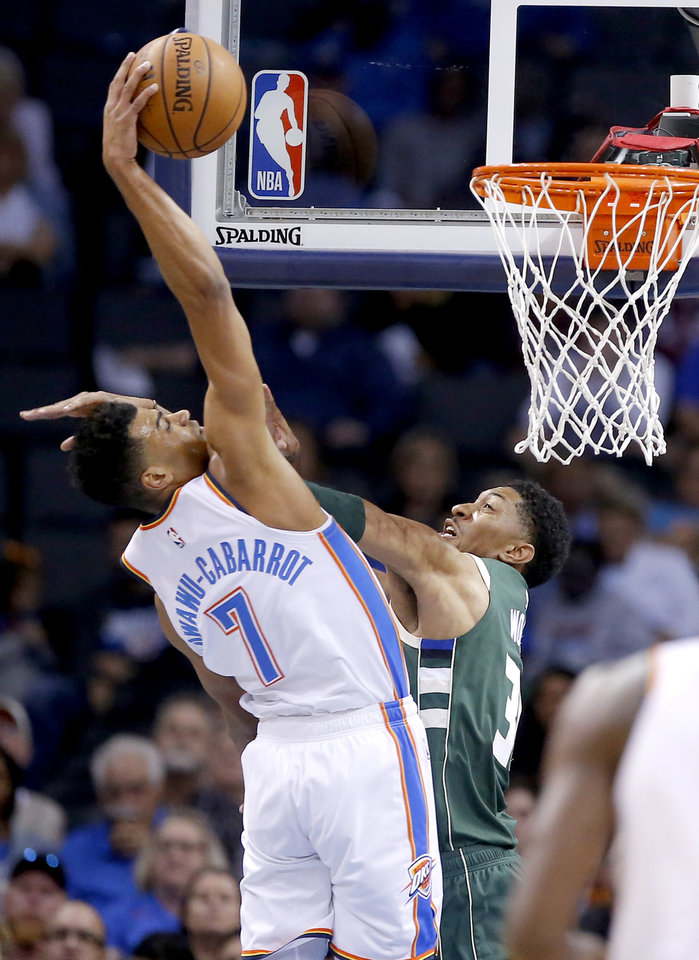 Photo - Oklahoma City's Timothe Luwawu-Cabarrot (7) dunks over Milwaukee's Christian Wood (35)  during a NBA preseason game between the Oklahoma City Thunder and Milwaukee Bucks at Chesapeake Energy Arena in Oklahoma City,  Tuesday, Oct. 9, 2018. Photo by Sarah Phipps, The Oklahoman