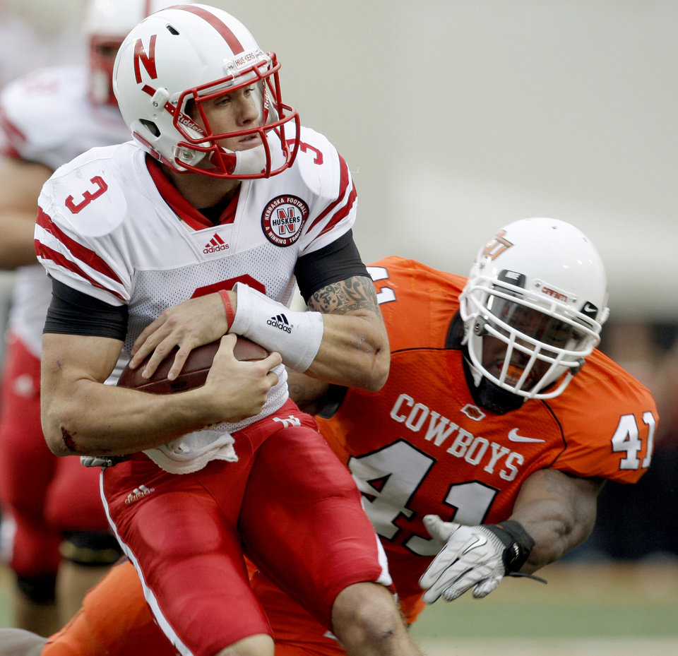Photo - Nebraska's  Taylor Martinez runs in front of OSU's Orie Lemon during the college football game between the Oklahoma State Cowboys (OSU) and the Nebraska Huskers (NU) at Boone Pickens Stadium in Stillwater, Okla., Saturday, Oct. 23, 2010. Photo by Bryan Terry, The Oklahoman