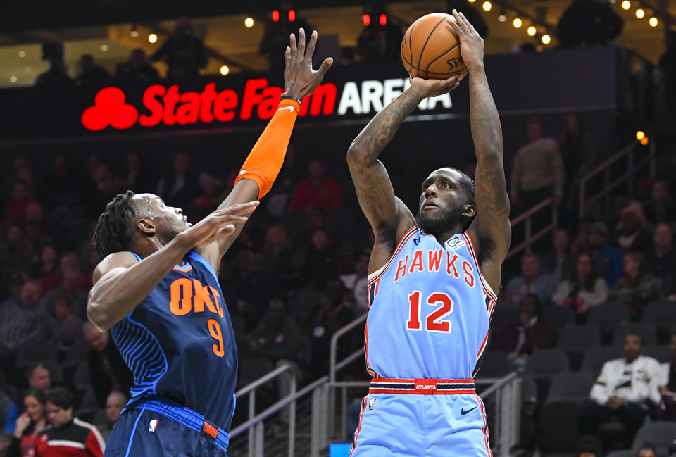 Photo - Atlanta Hawks forward Taurean Prince (12) shoots under pressure from Oklahoma City Thunder forward Jerami Grant during the second half of an NBA basketball game, Tuesday, Jan. 15, 2019, in Atlanta. (AP Photo/John Amis)