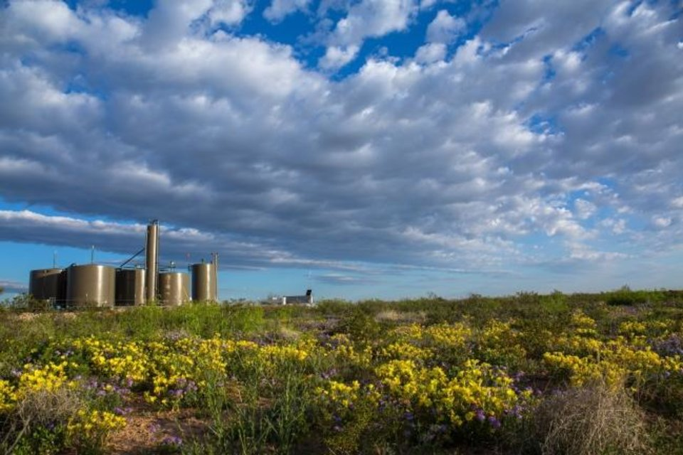 Photo -  A Devon Energy production pad in the Delaware Basin in southeastern New Mexico is shown. The company uses technology to monitor well operations, particularly when they are located in remote areas. [PROVIDED]