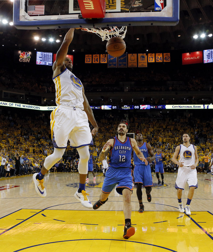 Photo - Golden State's Andre Iguodala dunks the ball in front of Oklahoma City's Steven Adams in the second half of Game 2 of the Western Conference finals. Adams and his fellow big men struggled on Wednesday night in a blowout loss to the Warriors. (Photo by Nate Billings, The Oklahoman)