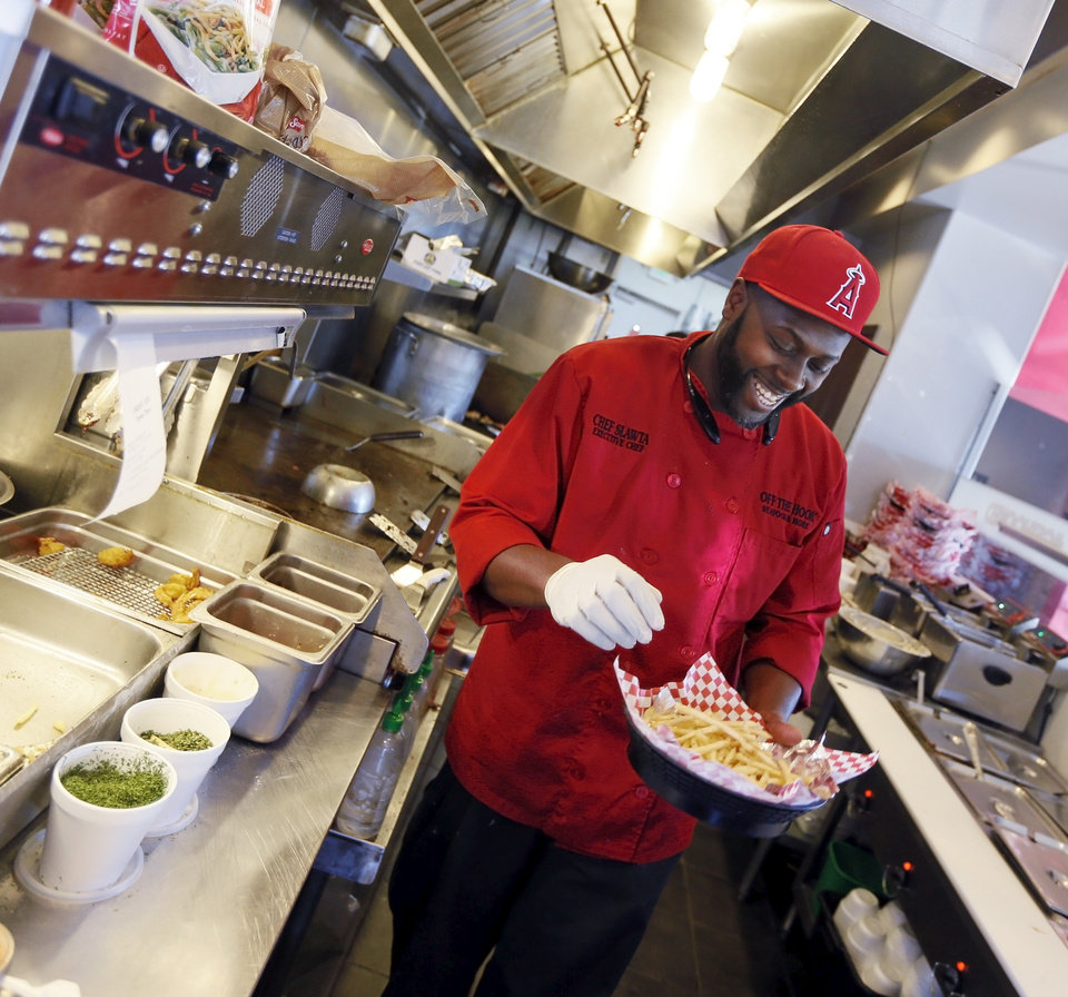 Photo - Chef Corey Harris makes smothered seafood fries at Off the Hook Seafood and More, 125 W. Britton Rd., in Oklahoma City, Wednesday, Feb. 15, 2017. Photo by Nate Billings, The Oklahoman