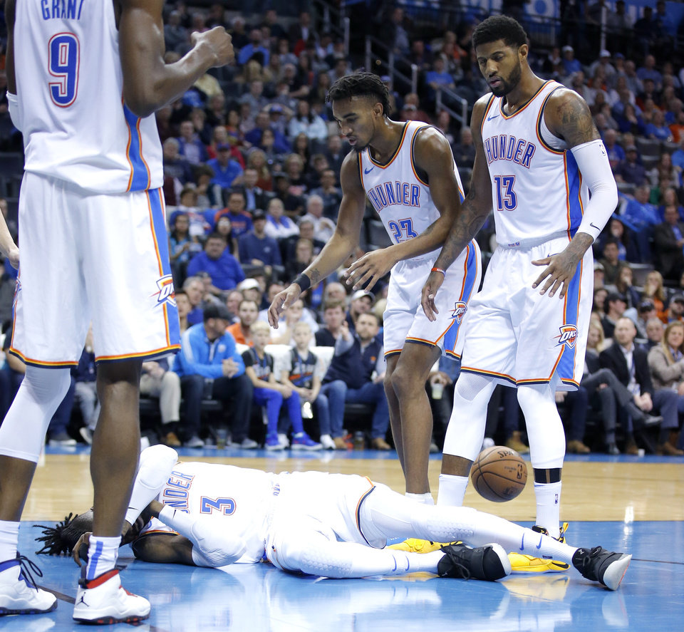 Photo - Oklahoma City's Terrance Ferguson (23) and Paul George (13) react as medical personal attend to Oklahoma City's Nerlens Noel (3) during the NBA game between the Oklahoma City Thunder and Minnesota Timberwolves at the Chesapeake Energy Arena, Tuesday, Jan. 8, 2019. Photo by Sarah Phipps, The Oklahoman