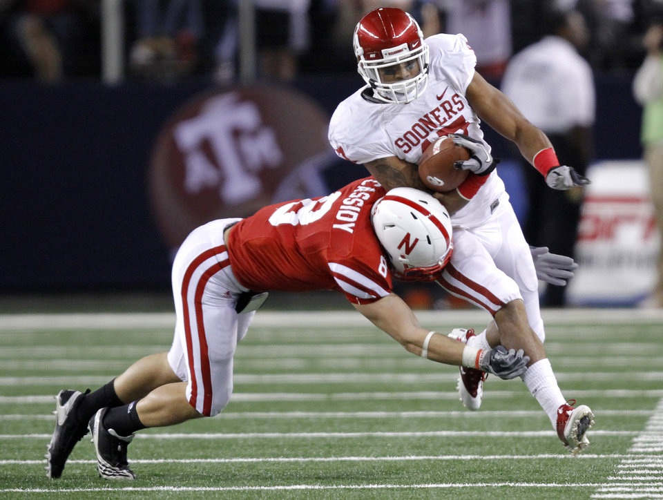 Photo - Oklahoma's Mossis Madu (17) is knocked out of bounds by Nebraska's Austin Cassidy (8) during the Big 12 football championship game between the University of Oklahoma Sooners (OU) and the University of Nebraska Cornhuskers (NU) at Cowboys Stadium on Saturday, Dec. 4, 2010, in Arlington, Texas.  Photo by Chris Landsberger, The Oklahoman