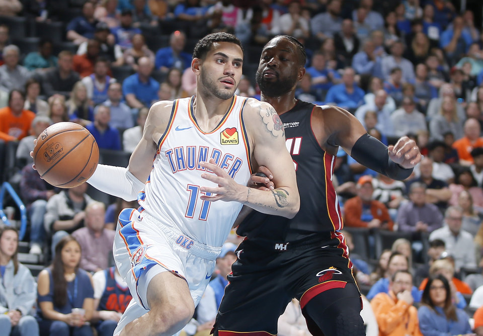 Photo - Oklahoma City's Abdel Nader (11) goes past Miami's Dwyane Wade (3) during an NBA basketball game between the Oklahoma City Thunder and the Miami Heat at Chesapeake Energy Arena in Oklahoma City, Monday, March 18, 2019. Photo by Bryan Terry, The Oklahoman