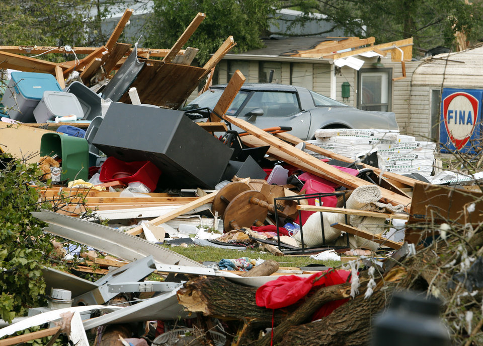 Photo - Jessica Wilkinson's car is under debris from her home after a tornado that struck near 156th street and Franklin Road on Sunday, May 19, 2013  in Norman, Okla. Photo by Steve Sisney, The Oklahoman