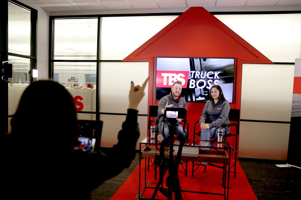 Photo -  Landon Middleton, left, and Isela Cuarenta host a video shoot as Niki Weibel records inside the TBS Factoring Service studio in Oklahoma City. [Photos by Bryan Terry, The Oklahoman]