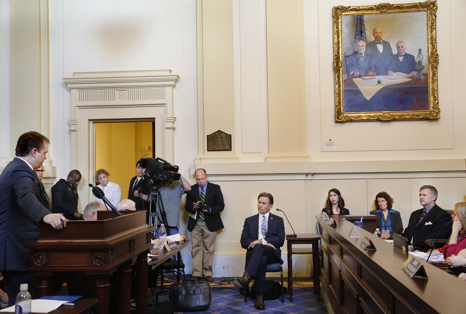 Photo - Mike Hunter, seated in center, answers  questions from attorney Garry Gaskins, standing at rostrum. Oklahoma Attorney General Mike Hunter can remain on the ballot after the Oklahoma Election Board voted 3-0 on Monday, April 23, 2018, to deny a challenge to his candidacy on residency grounds. Hunter, a Republican, testified he always kept Oklahoma as his permanent home even though he lived in Virginia for years while working in Washington, D.C. for two trade organizations.