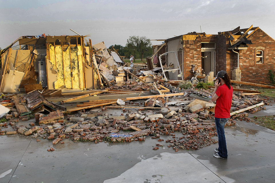 Photo - Ann Powell calls her insurance company while standing in front of what is left of her house at 306 Mounds, just south of Harrah Road and Reno Monday evening after tornadoes ripped through the area. Powell moved to Oklahoma about a year ago from California. Photo by Hugh Scott, The Oklahoman