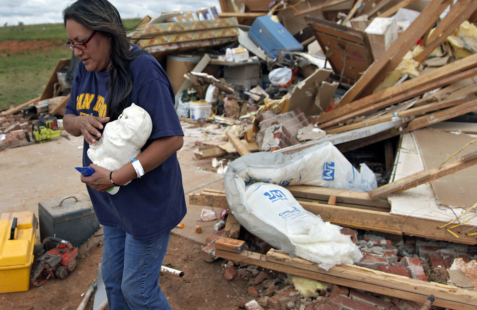 Photo - Susan Sleeper recovers one of her favorite items out of her destroyed home west of El Reno, Wednesday, May 25, 2011. Photo by Chris Landsberger, The Oklahoman