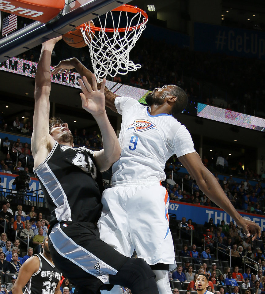 Photo - Oklahoma City's Serge Ibaka (9) blocks the shot of San Antonio's Boban Marjanovic (40) during anNBA basketball game between the Oklahoma City Thunder and the San Antonio Spurs at Chesapeake Energy Arena in Oklahoma City, Saturday, March 26, 2016. Photo by Bryan Terry, The Oklahoman
