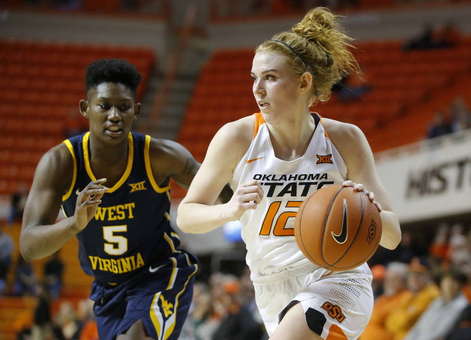 Photo - Oklahoma State's Vivian Gray (12) goes past West Virginia's Tynice Martin (5) during an NCAA women's basketball game between Oklahoma State University (OSU) and West Virginia at Gallagher-Iba Arena in Stillwater, Wednesday, Feb. 20, 2019. Photo by Bryan Terry, The Oklahoman