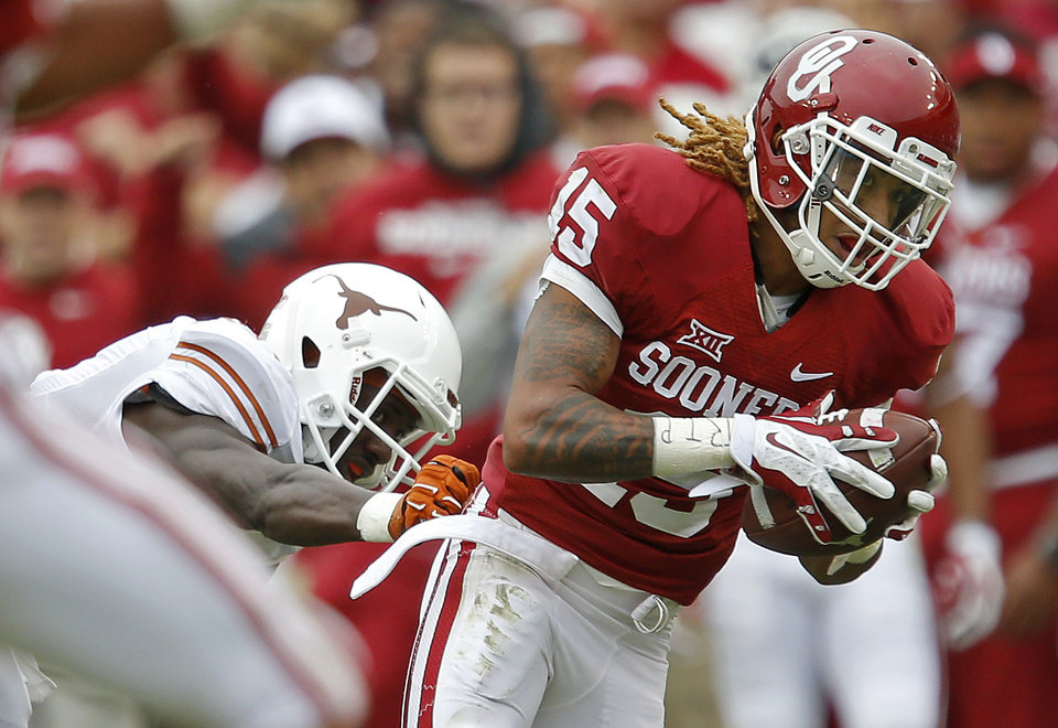 Photo - Oklahoma's Zack Sanchez (15) intercepts a pass in front of Texas' Jacorey Warrick (11) during the Red River Showdown college football game between the University of Oklahoma Sooners (OU) and the University of Texas Longhorns (UT) at the Cotton Bowl in Dallas on Saturday, Oct. 11, 2014. 