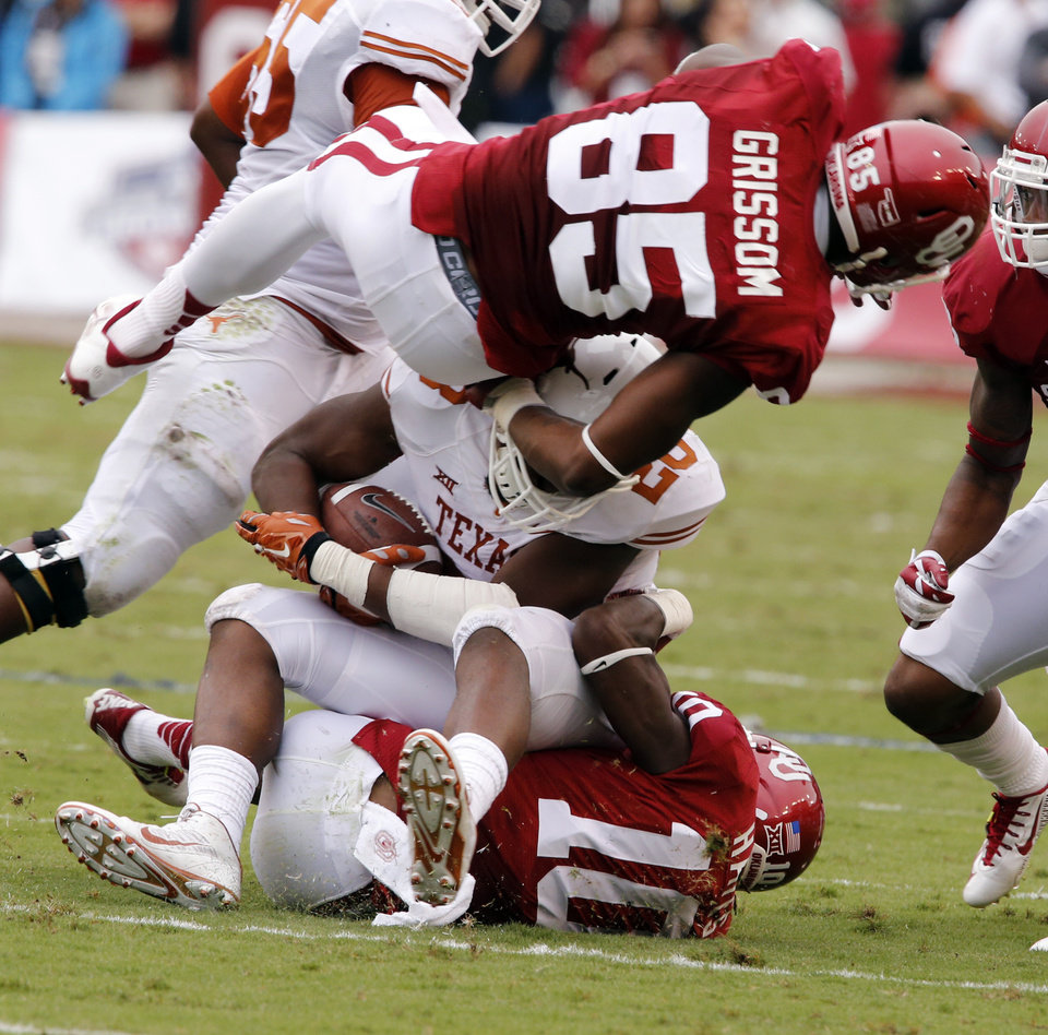 Photo - Oklahoma's Geneo Grissom (85) and Quentin Hayes (10) stop Texas' Malcolm Brown (28)  during the Red River Showdown college football game between the University of Oklahoma Sooners (OU) and the University of Texas Longhorns (UT) at the Cotton Bowl in Dallas, Texas on Saturday, Oct. 11, 2014. 