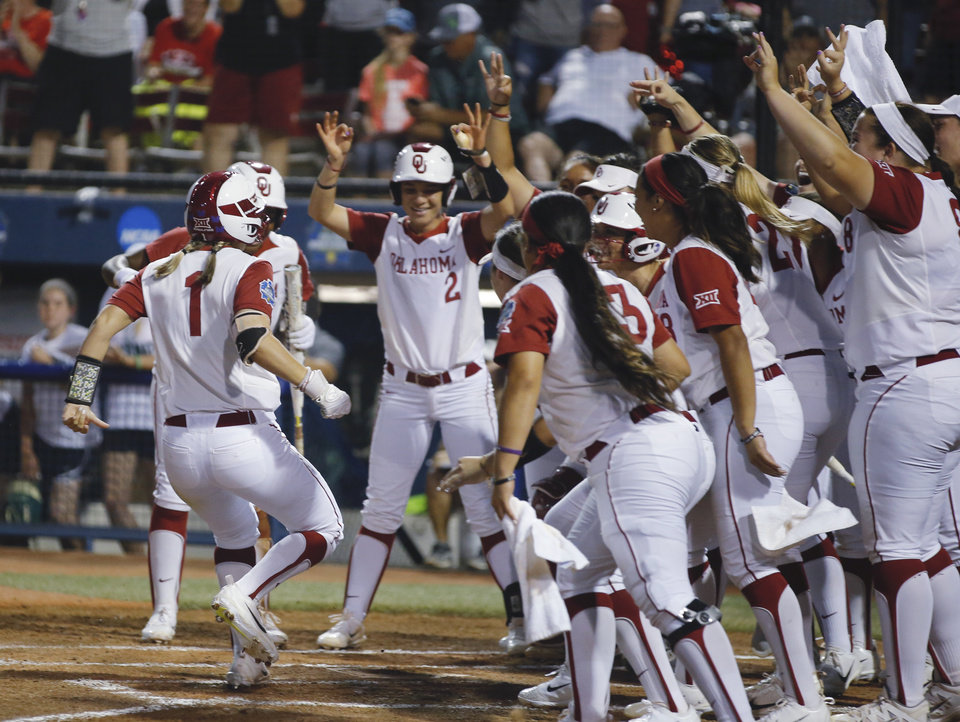 Photo -  After Nicole Pendley hit a home run in Thursday's game against Baylor, the OU softball team greeted her at home with threes raised up in celebration. [PHOTO BY BRYAN TERRY/The Oklahoman]