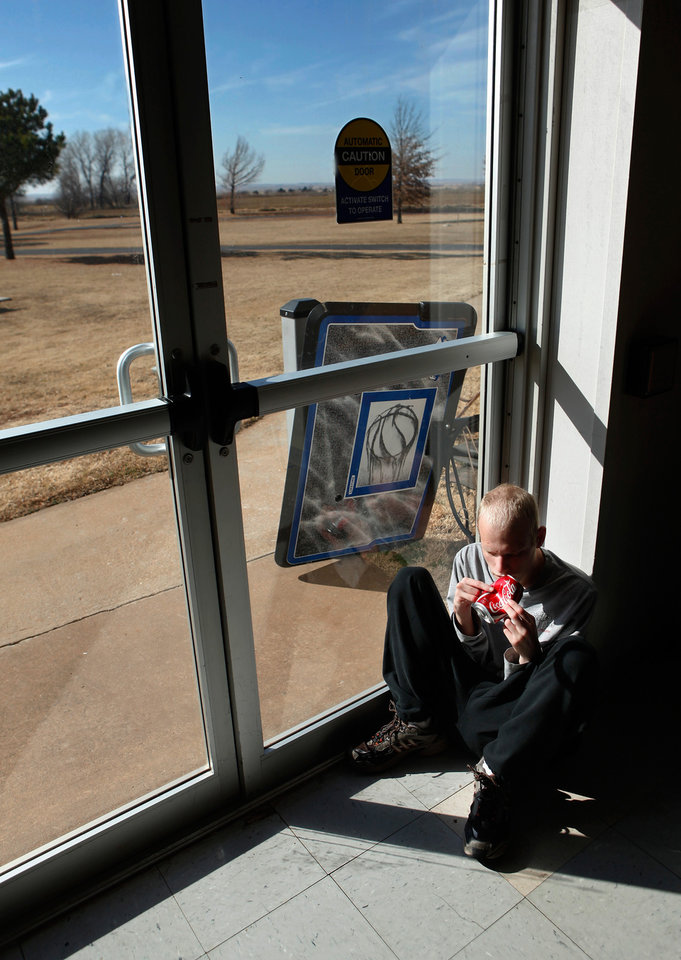 Photo - A resident sits in the sunlight poring through a glass door in the gymnasium/multi-purpose room at the 54-bed  facility, Center of Family Love, a group home for mentally disabled people, in Okarche on Monday, Jan. 18, 2010.   Photo by Jim Beckel, The Oklahoman