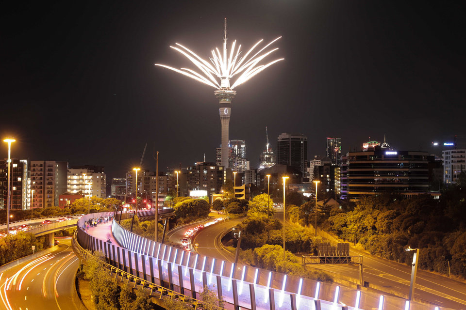 Photo -  Fireworks are launched from the Sky Tower to mark the changing of the year on New Year's eve in Auckland, New Zealand, Thursday. New Zealand and its South Pacific island neighbors have no COVID-19, and New Year celebrations there are the same as ever. [Michael Craig/NZ Herald via AP]