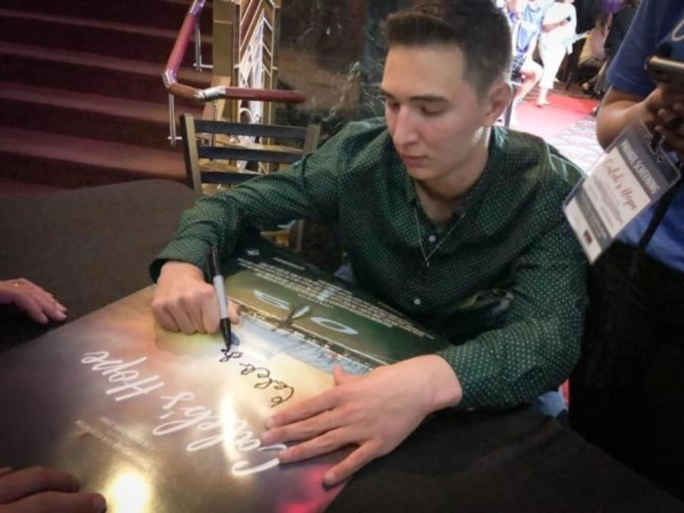 Photo -  Caleb Freeman, of Newcastle, signs movie posters at Monday's screening of