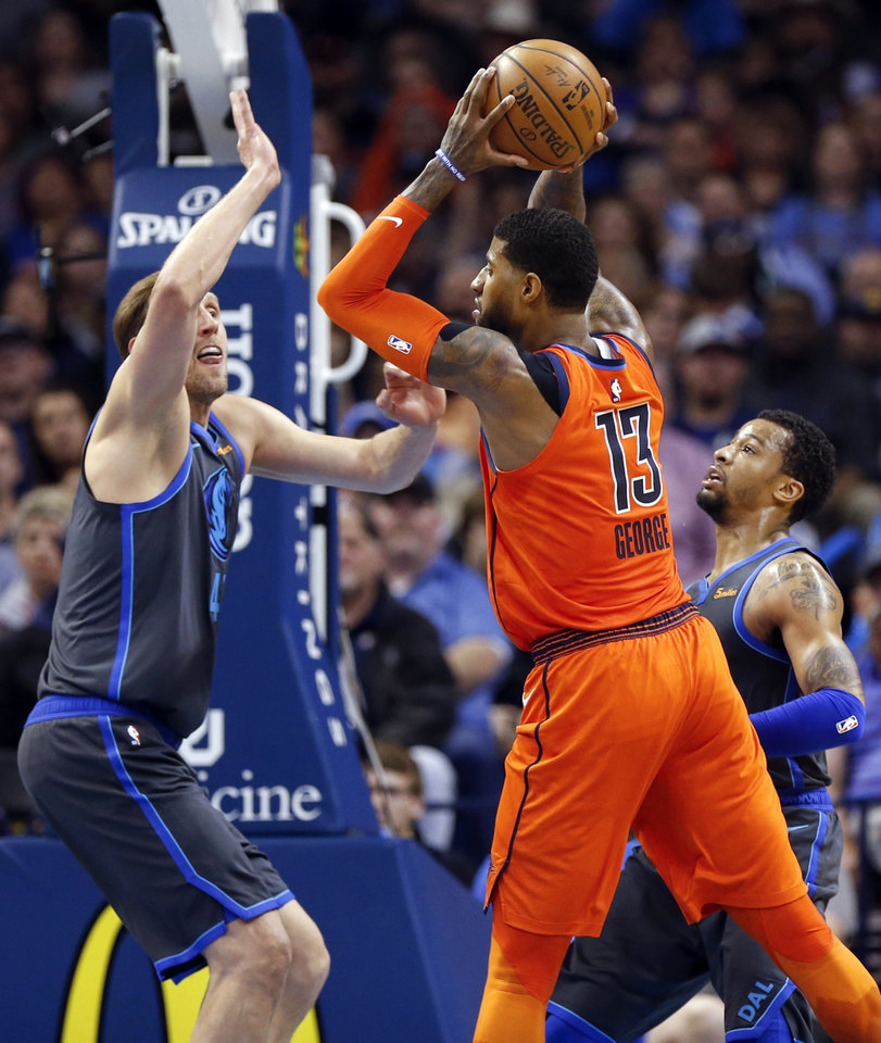 Photo - Oklahoma City's Paul George (13) passes between Dallas' Trey Burke (23), right, and Dirk Nowitzki (41) in the fourth quarter during an NBA basketball game between the Dallas Mavericks and the Oklahoma City Thunder at Chesapeake Energy Arena in Oklahoma City, Sunday, March 31, 2019. Dallas won 106-103. Photo by Nate Billings, The Oklahoman