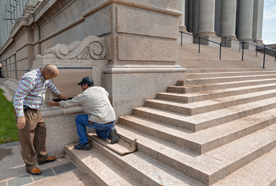 Photo - Crews use cardboard to cover graffiti at the Oklahoma state Capitol on Monday, June 1, 2020, in Oklahoma City, Okla. that was left behind after the George Floyd protest on Sunday.    [Chris Landsberger/The Oklahoman]